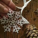 Weihnachtliche Dekoration aus Spitze und Tannenzapfen